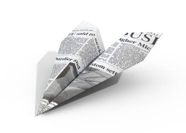 Newspaper folded as a paper airplane